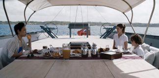 Donna, ragazza, bambino fanno colazione in barca a vela
